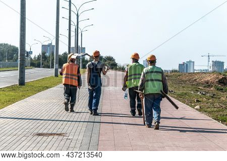 A Team Of Workers In Helmets And Overalls With Shovels Go To The Place Of Work. Work In An Urban Env