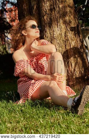 Beautiful Pinup Girl With Red Dress And Curly Red Hair Sitting Near Tree At Sunny Park In Sun Light