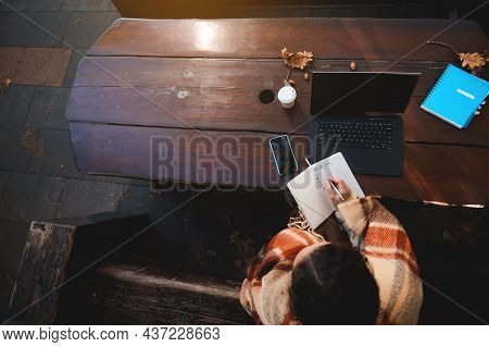 Overhead View Of A Woman Writing In Notebook While Sitting On A Wooden Bench In Front Of A Laptop An