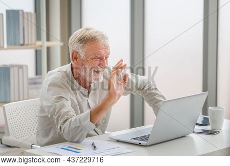 Portrait Of Senior Man Using Laptop Using Laptop Talking On Video Call At Home, Happy Senior Man In