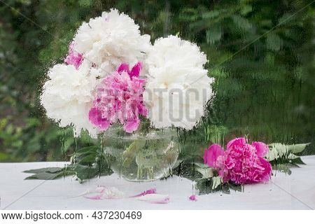 Pink And White Flowers Behind A Wet Window With Raindrops, Blurred Street Bokeh. The Concept Of Spri