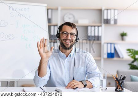 Glad Middle Aged European Man In Glasses And Headphones Waving Hand To Webcam