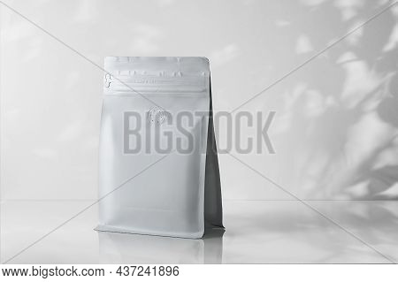 Mock-up Of A Coffee Package On A Gray Background With Stiff Shadows From The Leaves.
