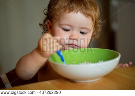 Funny Baby Eating Food Himself With A Spoon On Kitchen. Healthy Nutrition For Kids.
