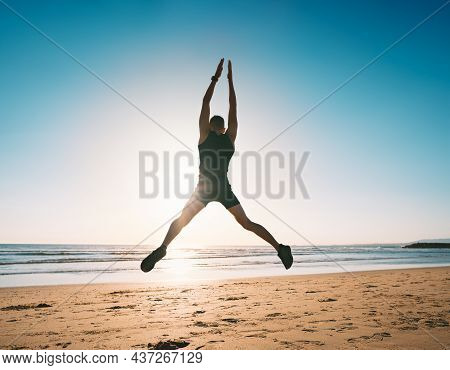 Jumping Man. Young Fitness Man Doing Jumping Jacks Or Star Jump Exercise On The Beach