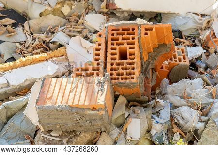 Close-up Of Red Brick Debris, Plastic Waste And Other Construction Waste In An Illegal Landfill. Env