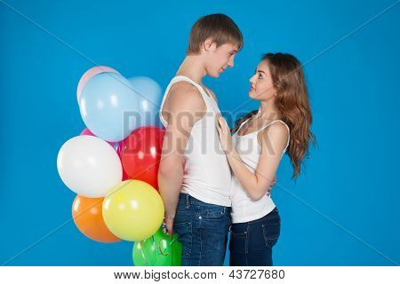Smiling Young Love Couple Holding  Balloons In The Studio