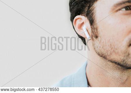 American man listening to music on wireless earphones closeup