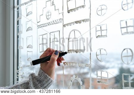 Female Hand Draws Christmas Holidays Decoration On Window Glass. New Years Scenery. City Buildings G