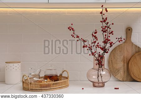 Hawthorn Branches With Red Berries In Vase And Aromatic Tea On White Table Indoors