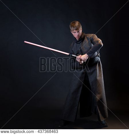 A Villain With A Red Lightsaber, A Young Man In A Long Robe Does Fighting Poses, Fantasy Or Science