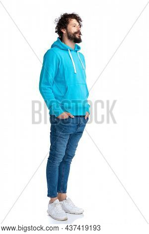 cool bearded guy in blue hoodie holding hands in pockets and waiting in line while posing on white background in studio