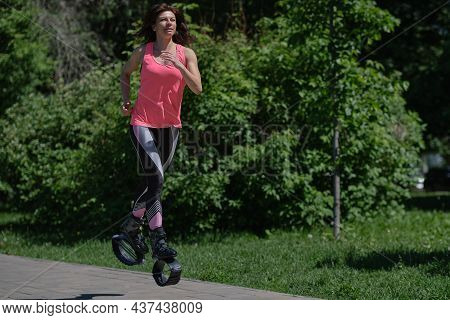 Beautiful Woman Runs Along The Path In The Park, Legs In Kangoo Jumping Shoes. Women Training Kangoo