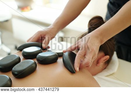 Part of body of young female with hot spa stones on her back and professional masseuse holding two of them