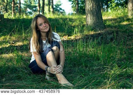 Teen girl sitting on the green grass in the park in the summer.