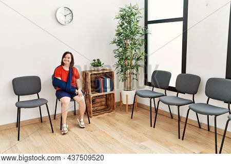 Brunette woman with down syndrome sitting wearing arm on sling at waiting room