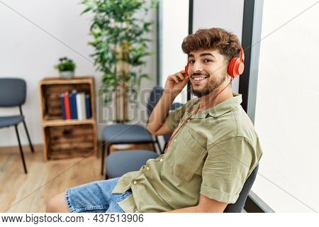 Young arab man listening to music sitting on the chair at waiting room