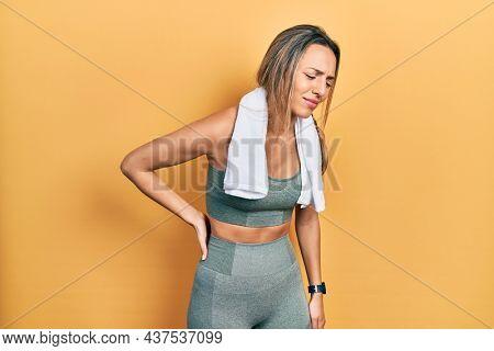 Beautiful hispanic woman wearing sportswear and towel suffering of backache, touching back with hand, muscular pain