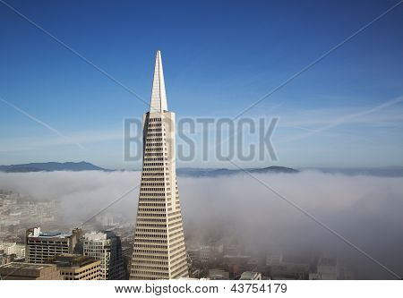 real view on Transamerica pyramid and city of San Francisco covered by dense fog