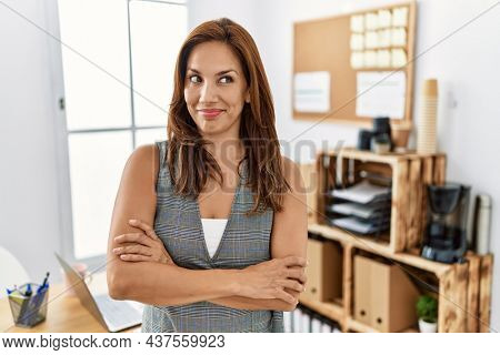 Middle age hispanic woman at the office smiling looking to the side and staring away thinking.