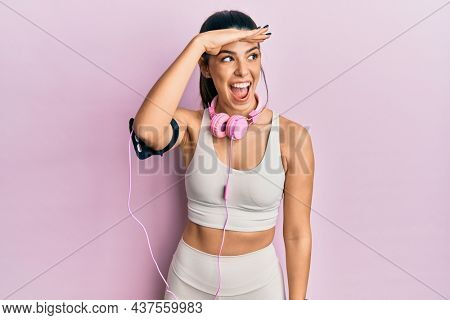 Young hispanic woman wearing gym clothes and using headphones very happy and smiling looking far away with hand over head. searching concept.