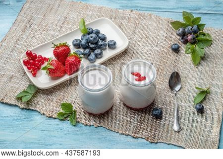 Two glass containers with plain yoghurt and berries on the table. Light summer mood.