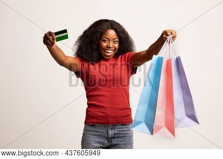 Easy Shopping. Excited Happy Black Lady With Credit Card And Shopper Bags