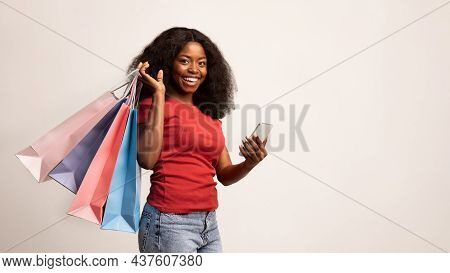 Shopping App. Cheerful Black Female Holding Smartphone And Bright Paper Shopper Bags