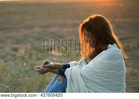 Pensive Young Woman Wrapped In Warm Blanket Sit Outdoors At Sunset. Thoughtful Female Alone In Natur