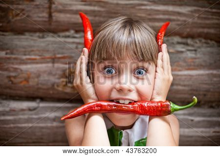 Girl With A Red Hot Chili Pepper In Her Mouth Show Devil Horns