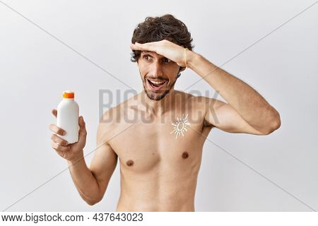Young hispanic man standing shirtless holding sunscreen lotion very happy and smiling looking far away with hand over head. searching concept.