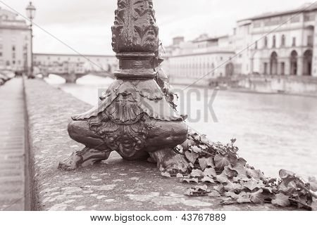 Lamppost Base And The Ponte Vecchio Bridge With River Arno, Florence