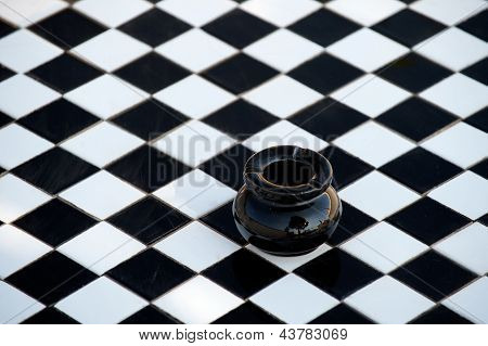 Black and white checkered table with black ashtray