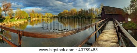 a wooden Watermill at sunset - panoramic view poster