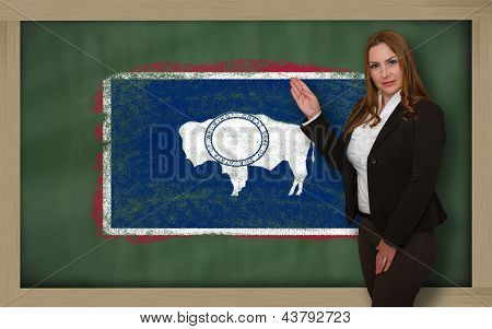 Teacher Showing Flag Ofwyoming On Blackboard For Presentation Marketing And Tourist Advertising