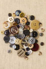 Pile Of Neutral Brown Buttons On Hessian