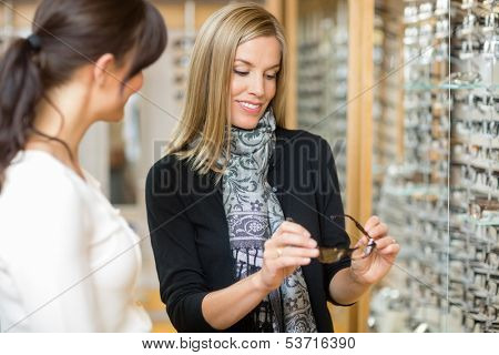 Young woman examining eyeglasses with salesgirl in optician store