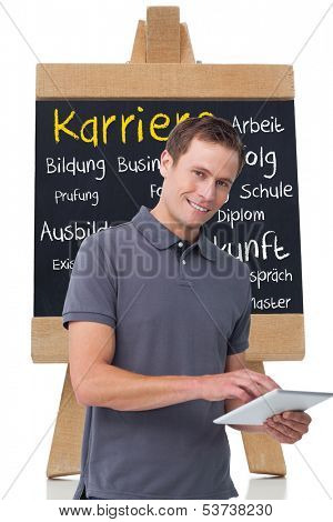 Composite image of smiling young man in front of chalk board with german terms about career written on it