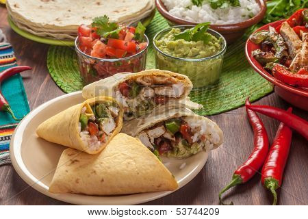 traditional mexican food: cilantro and lime rice, chicken fajitas, fajita peppers, burritos, tortillas, guacamole and salsa
