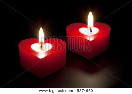 Heart shaped candles isolated on black background poster