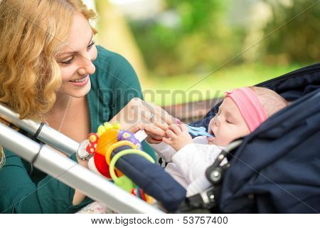 Cheerful mother giving her baby toy for baby teething