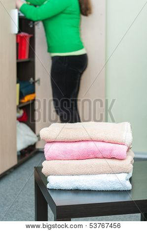Stack Of Towels On Table In Foreground And Housewife In Background
