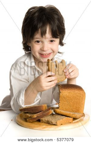 The Little Boy Which Eating A Bread On Desk