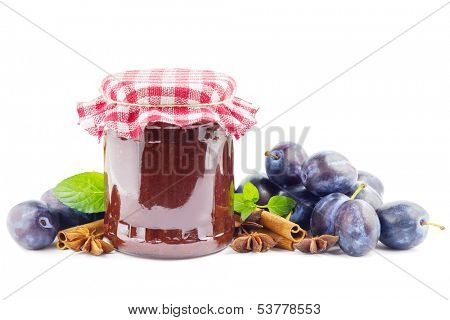 Jar with plum butter, plums and spices on white