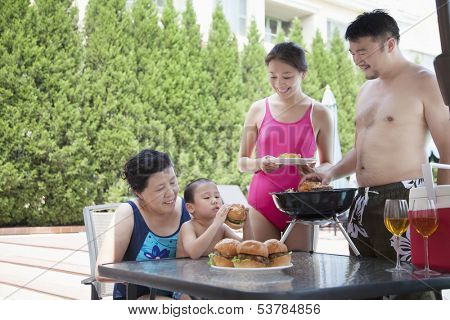 Smiling multi-generational family barbequing by the pool on vacation