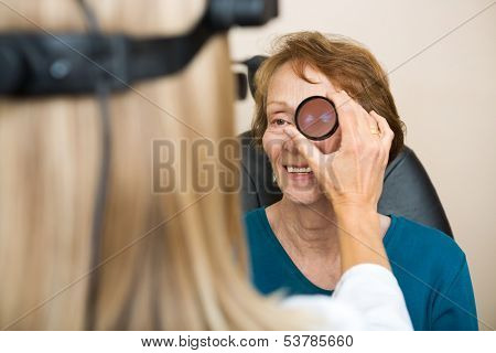 Female optician examining senior woman's eye with binocular indirect ophthalmoscope