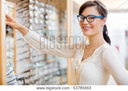 Portrait of happy young woman buying new glasses at optician store