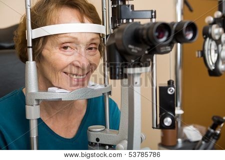 Smiling senior woman undergoing eye examination test with slit lamp in store poster