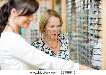 Salesgirl assisting senior woman in selecting glasses at optician store