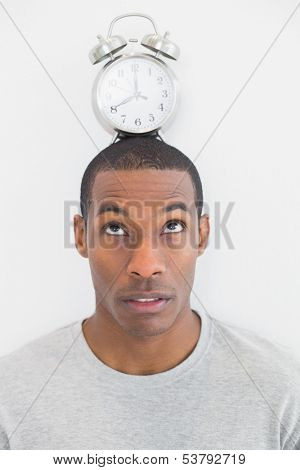 Close up of a man with an alarm clock on top of his head over white background